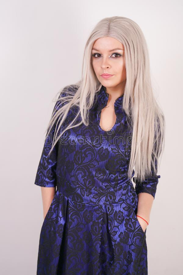 Beautiful blonde girl in luxurious blue with black lace evening dress on white background in Studio. Isolated stock images