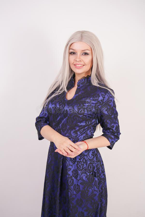 Beautiful blonde girl in luxurious blue with black lace evening dress on white background in Studio. Isolated stock photography