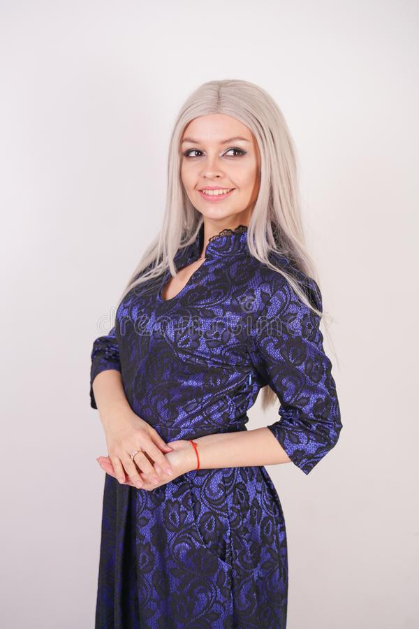 Beautiful blonde girl in luxurious blue with black lace evening dress on white background in Studio. Isolated stock photo