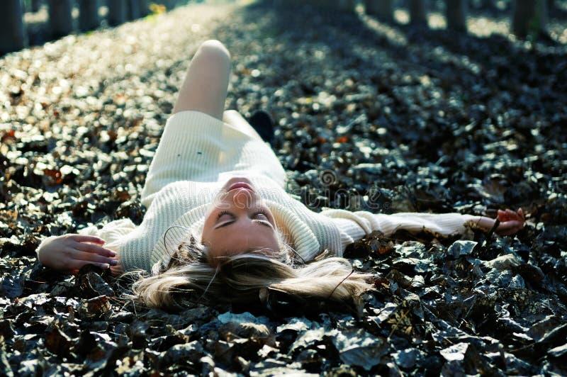 Beautiful blonde girl lying on leaves stock photo