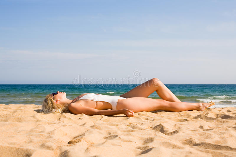 Beautiful blonde girl lying on sand stock images