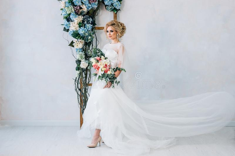 Beautiful blonde girl with beautiful make-up and hairstyle posing in white wedding dress against a white wall background with a f. The bride stands on a white stock photos