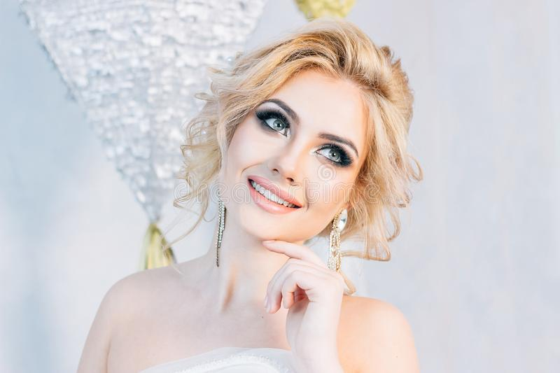 Beautiful blonde girl with beautiful make-up and hairstyle posin. The bride stands on a white wall background stock image