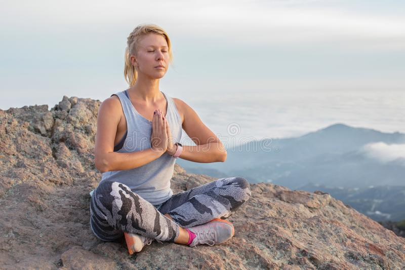 Beautiful blonde girl meditating on the top of the high rocky mountain in Malibu, USA stock images