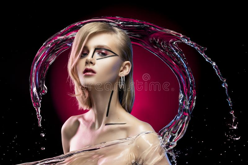 Beautiful blonde girl with naked shoulders and avant-garde conceptual makeup, surrounded by splashes and drops of water stock photo