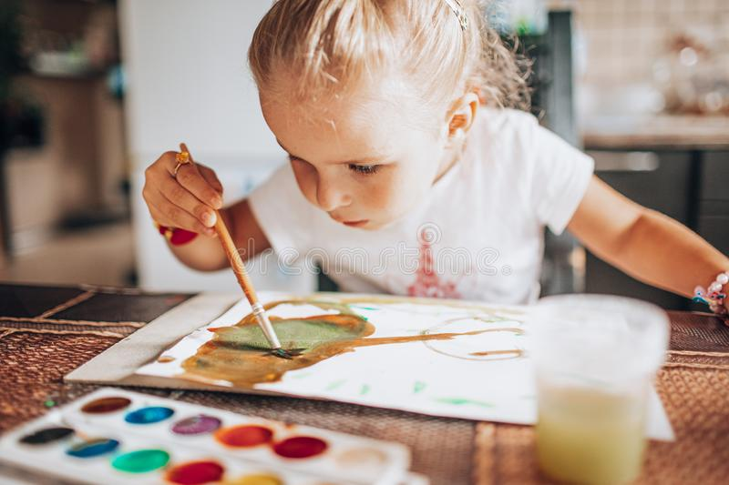 Beautiful blonde girl painting with paintbrush and water colors in the kitchen. Kid activities concept. Close up. Toned stock photo