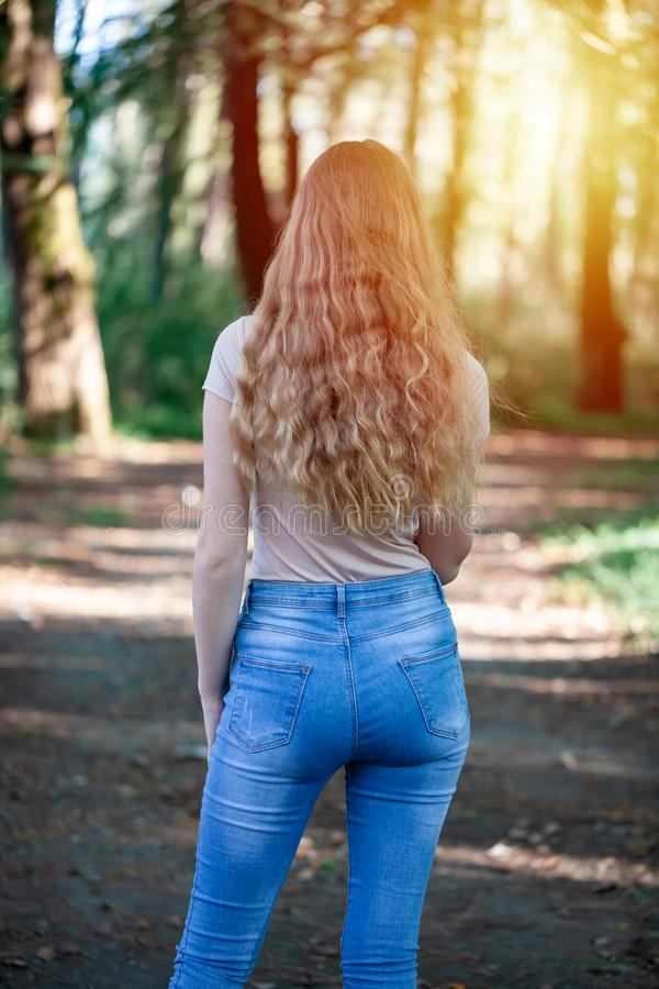 Beautiful blonde girl in the park. Portrait from the back stock image