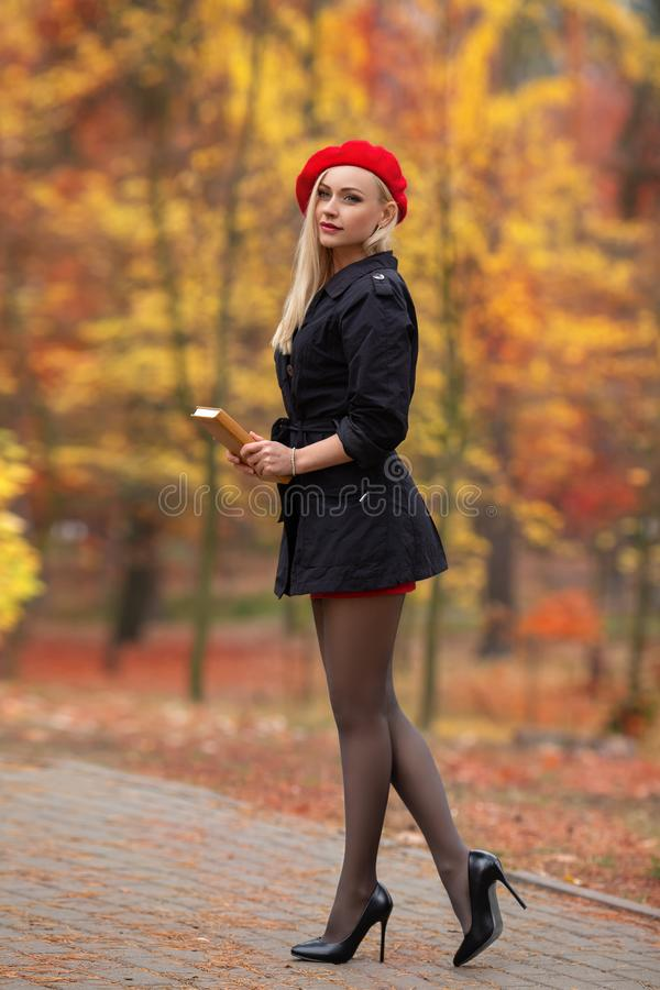Beautiful blonde girl with perfect legs and red beret posing outdoor on the street of autumn park. Modern Little Red Riding Hood. In the forest stock photo