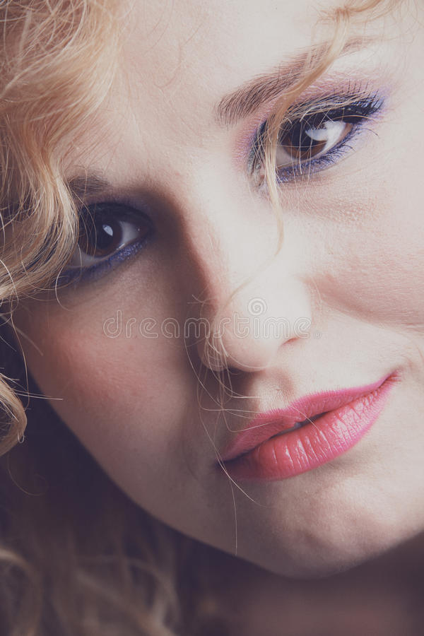 Beautiful blonde girl. Portrait of a young, gorgeous looking blonde woman with curly hair and pink make-up stock photo