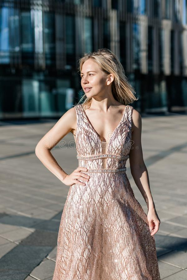 Beautiful blonde girl posing in a long beige dress on the background of a modern building stock photos