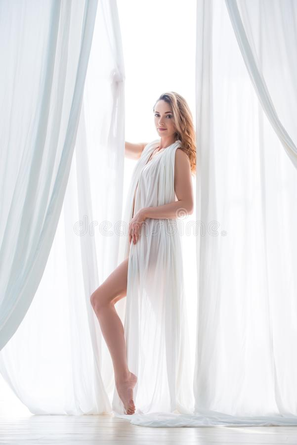 Beautiful blonde girl posing in white cloth. Women`s sensuality and beauty royalty free stock images