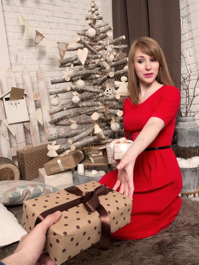 Beautiful blonde girl in red dress and New Year presents. New Year mood and interior. stock images