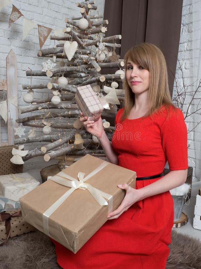 Beautiful blonde girl in red dress and New Year presents. New Year mood and interior. stock image