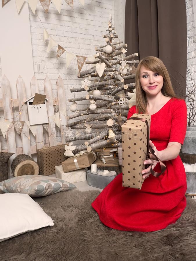Beautiful blonde girl in red dress and New Year presents. New Year mood and interior. royalty free stock images