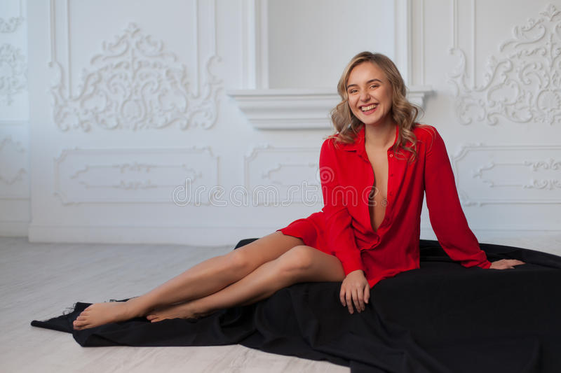 Beautiful blonde girl in a red shirt in the white interior sits on the floor in a black cloth stock photos