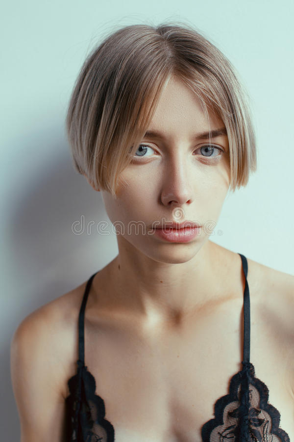 Beautiful blonde girl with short hairdo. Beautiful emotional girl with clean skin and short hair royalty free stock images