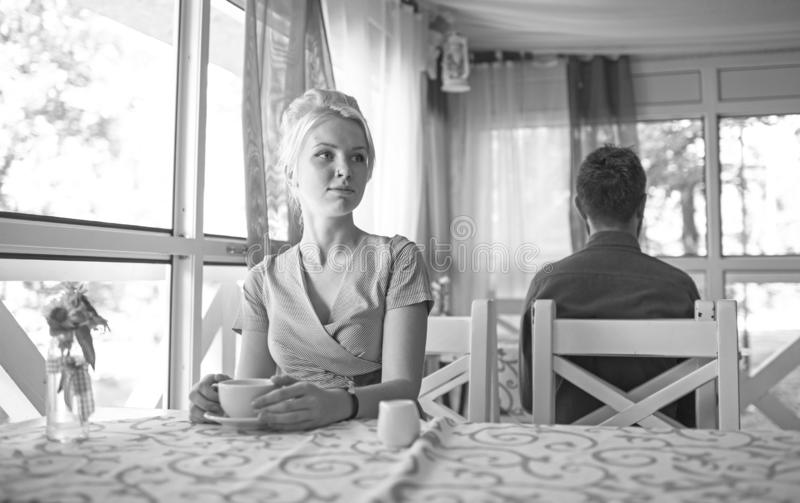 Beautiful blonde girl sits in cafe at table, holds mug stock image