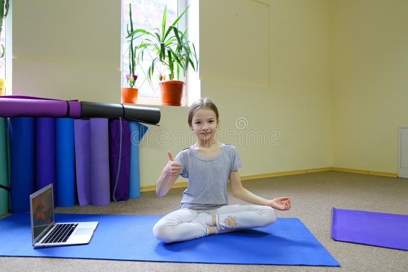 Little girl sits on floor in lotus position. stock image