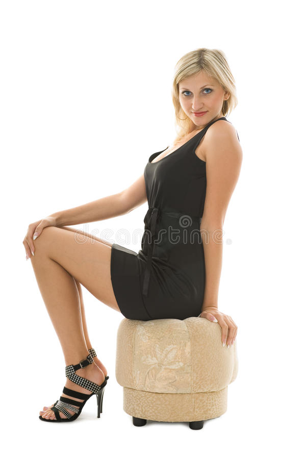 Beautiful blonde girl is sitting on an ottoman stock photography