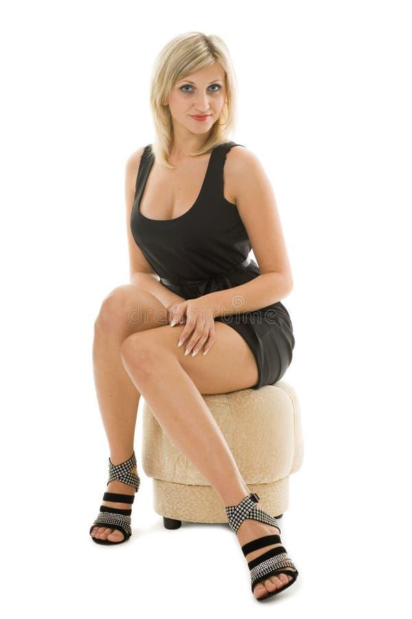 Beautiful blonde girl is sitting on an ottoman stock photos