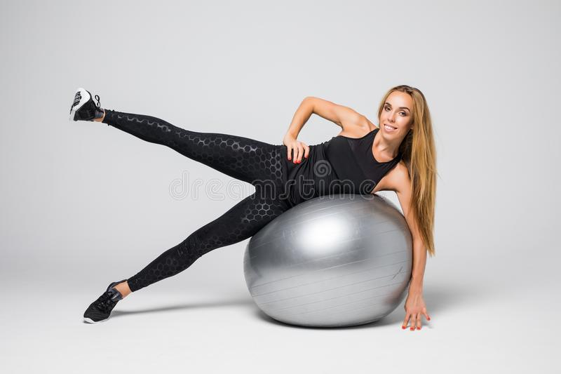 Beautiful blonde girl in sports clothes sitting on a fitness ball on a white background. Beautiful blonde girl in sports clothes sitting on a fitness ball on a stock photos