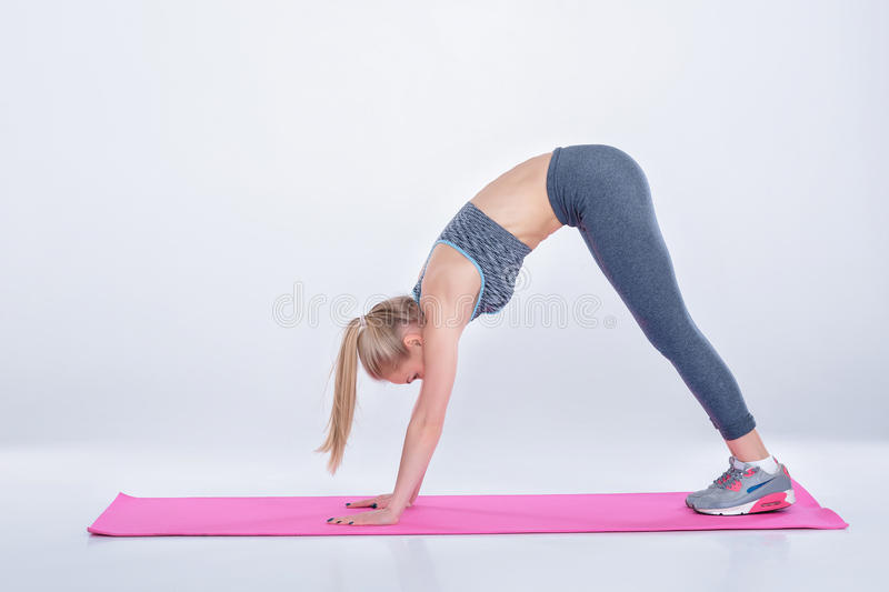Beautiful blonde girl in sportswear does exercises on fitness Mat. woman practicing yoga royalty free stock images