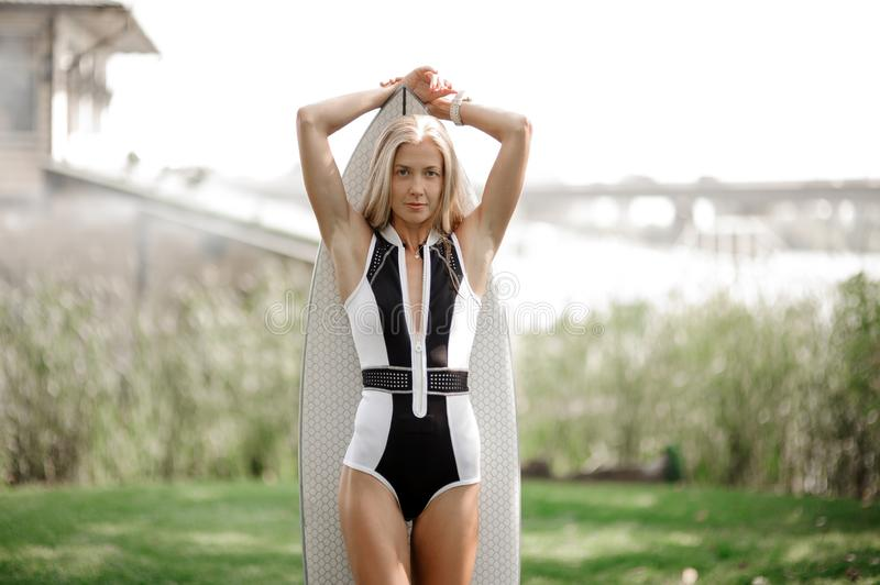 Beautiful blonde girl standing with the wakeboard. Beautiful blonde girl in black and white swimsuit standing with the wakeboard on the blurred background of old stock image