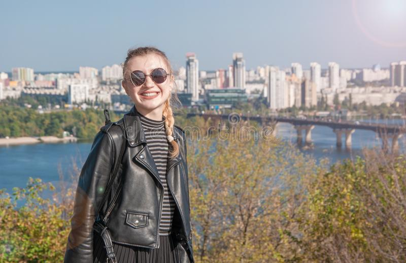Beautiful blonde girl stands on the background of the city and smiles royalty free stock photo