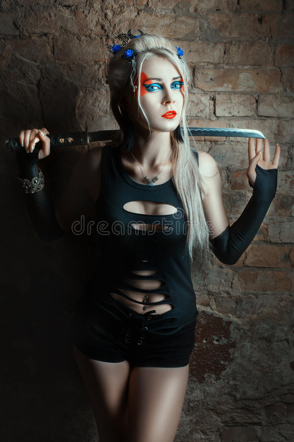 Beautiful blonde girl with a sword in his hand. On the face makeover warrior royalty free stock photos