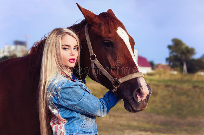 Beautiful blonde girl taking care of the horse at the ranch stock photos