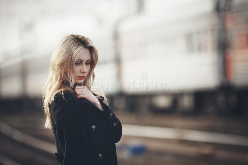 Beautiful blonde girl waiting for the train at the station. romantic, delicate look.  royalty free stock photography