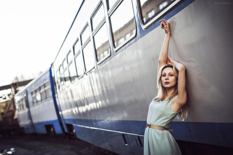 Beautiful blonde girl waiting for the train at the station. romantic, delicate look.  royalty free stock image