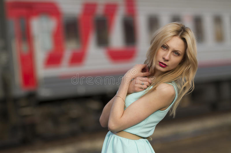 Beautiful blonde girl waiting for the train at the station. romantic, delicate look.  stock image