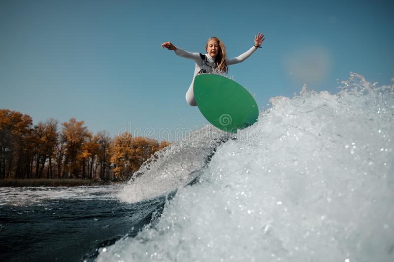 Blonde girl jumping on the green wakeboard on the bending knees. Beautiful blonde girl in the white swimsuit jumping on the green wakeboard on the bending knees stock images
