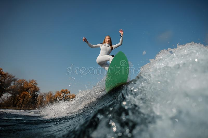 Blonde girl riding on the green wakeboard on the bending knees. Beautiful blonde girl in the white swimsuit riding on the green wakeboard on the bending knees stock photography