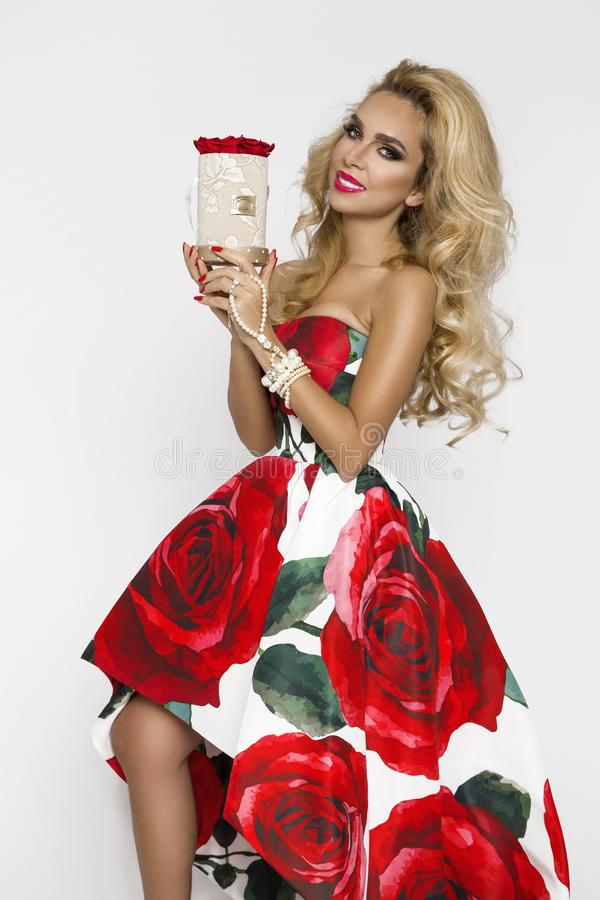 Beautiful blonde woman in an elegant evening gown with red roses, holding a Valentine`s gift, a flowerbox with flowers. Beauty. Beautiful blonde girl woman in an stock images