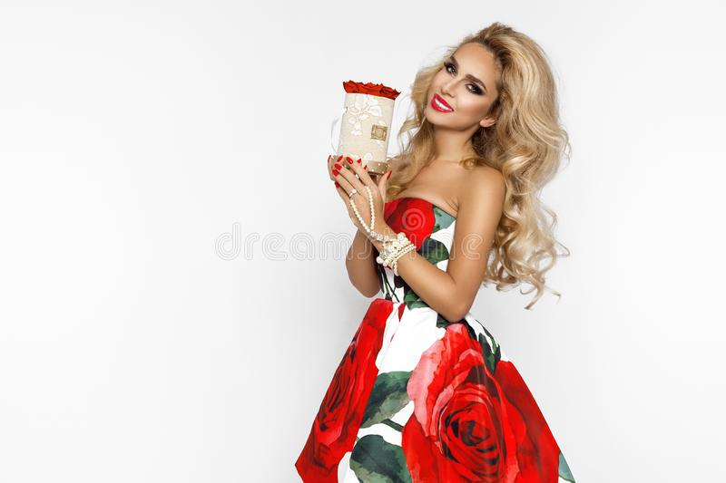 Beautiful blonde woman in an elegant evening gown with red roses, holding a Valentine`s gift, a flowerbox with flowers. Beauty. Beautiful blonde girl woman in an royalty free stock photos