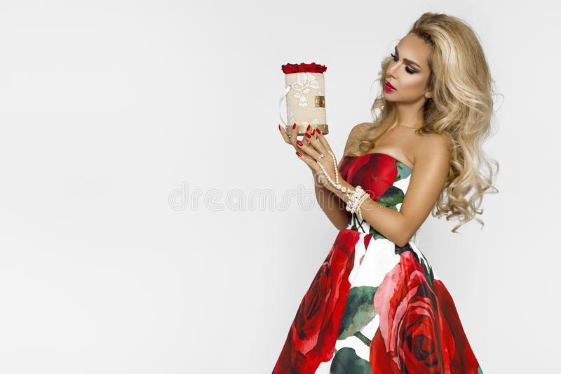 Beautiful blonde woman in an elegant evening gown with red roses, holding a Valentine`s gift, a flowerbox with flowers. Beauty. Beautiful blonde girl woman in an royalty free stock photo