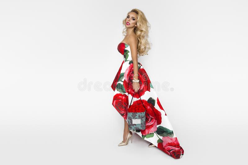 Beautiful blonde woman in an elegant evening gown with red roses, holding a Valentine`s gift, a flowerbox with flowers. Beauty. Beautiful blonde girl woman in an royalty free stock photography