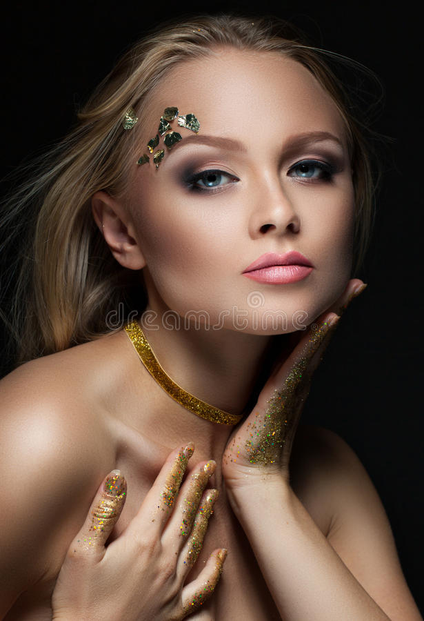Beautiful blonde with golden make-up. Beauty fashion. Face close-up stock photo