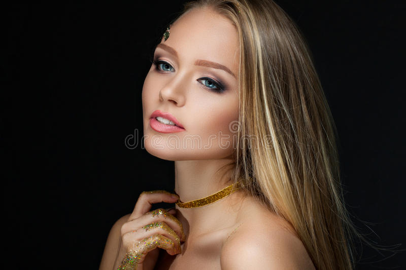Beautiful blonde with golden make-up. Beauty fashion. Face close-up royalty free stock photo