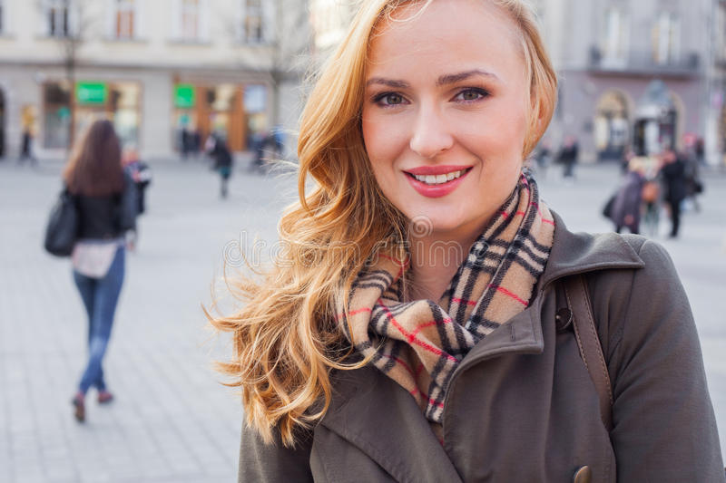 Beautiful blonde happy woman walking on the street in city. Outdoor photo. royalty free stock photo