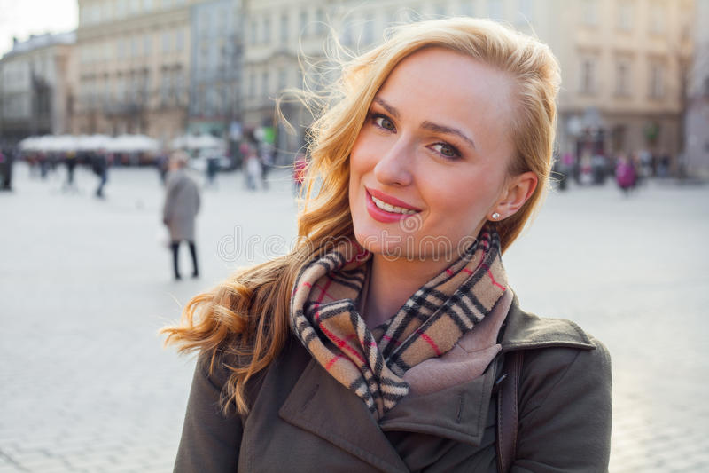 Beautiful blonde happy woman walking on the street in city. Outdoor photo. royalty free stock images