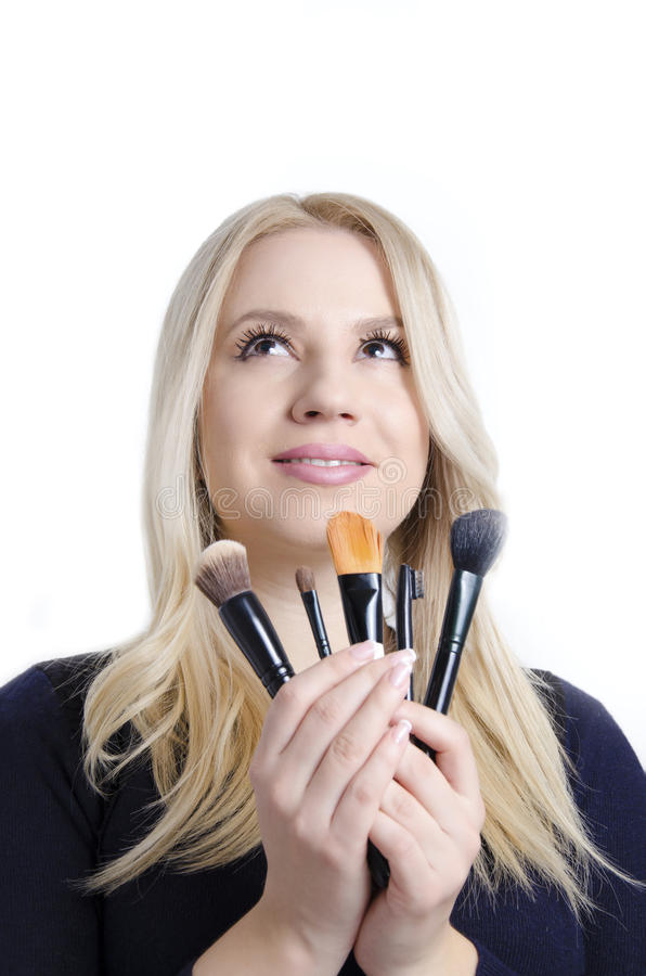 Beautiful blonde holding five professional makeup brushes royalty free stock photos