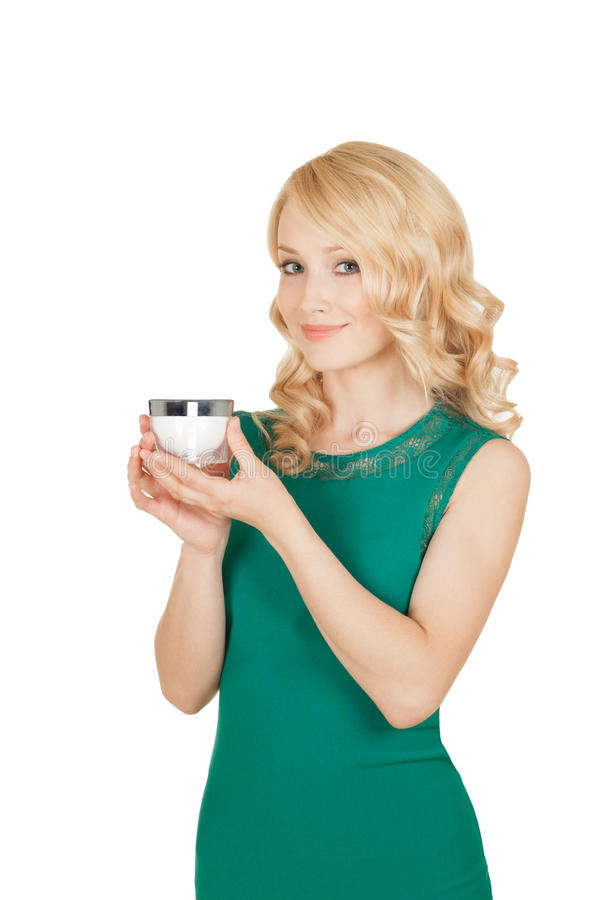 The beautiful blonde holds a cream jar in a hand. Beautiful blonde holds a cream jar in a hand royalty free stock images