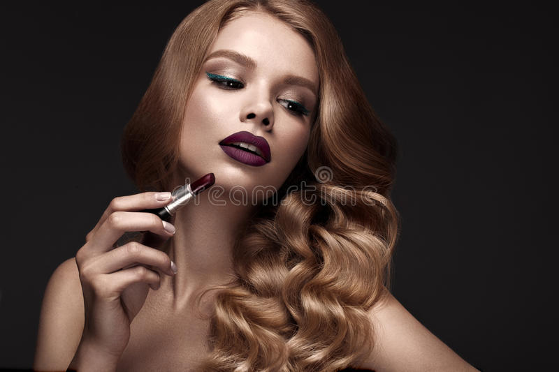Beautiful blonde in a Hollywood manner with curls, dark lips, lipstick in hand. Beauty face and hair. Picture taken in the studio stock image