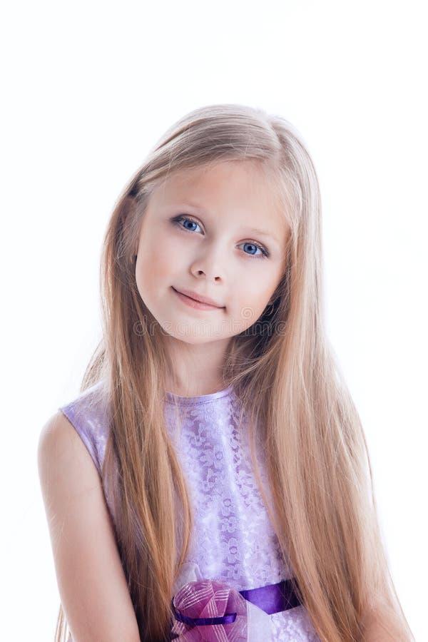 Beautiful blonde little girl in purple dress stock image