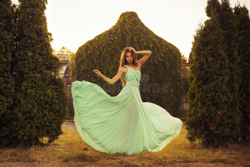 Beautiful blonde with a long curly hair in a long evening dress in motion outdoors near retro vintage building in summer sunset stock photo