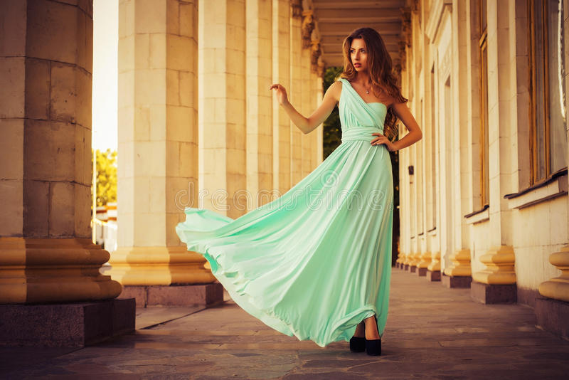 Beautiful blonde with a long curly hair in a long evening dress in static outdoors near retro vintage building in summer sunset royalty free stock images
