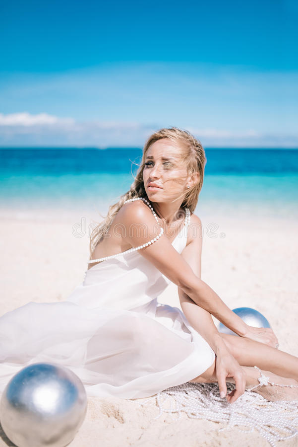 Beautiful blonde long hair bride in long white dress sitting on the white sand beach with a pearl.  stock photography